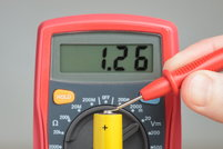 A multimeter reading a battery.