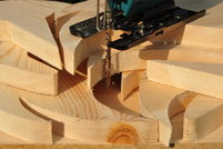 A jigsaw cutting rounded pieces of wood.