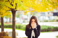 A woman blowing her nose into a tissue with a yellow-leaved tree behind her in the fall.