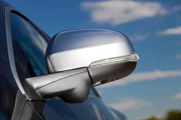 A car side mirror against a blue sky.
