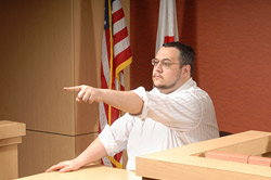 Man on the witness stand pointing finger