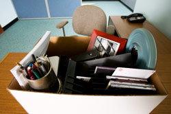 A box of belongings on an empty desk