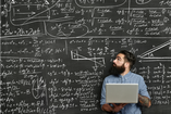 student with laptop in front of chalkboard