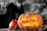 carved pumpkin in front of haunted house