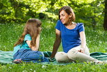mom and daughter sitting on picnic blanket talking