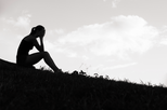 black and white silhouette of sad woman sitting on a hill