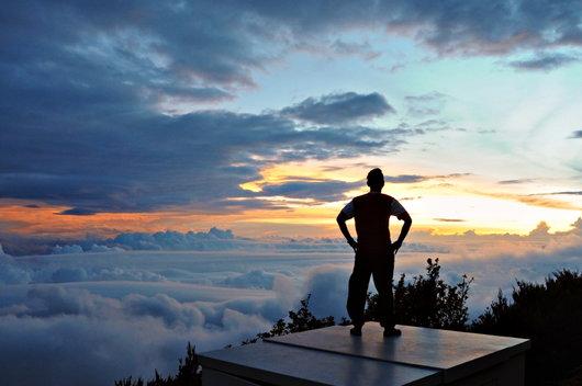 man standing on platform looking at ocean