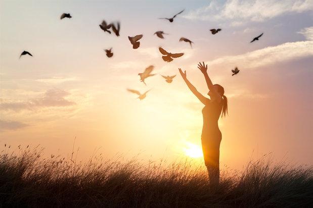 woman prays as birds fly