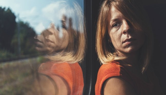Woman adult child of alcoholic looks out a window