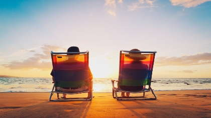 A retired couple sits on a beach together watching the sunset.