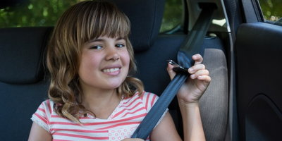 girl buckling seat belt in back seat