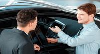 car salesperson showing customer a car