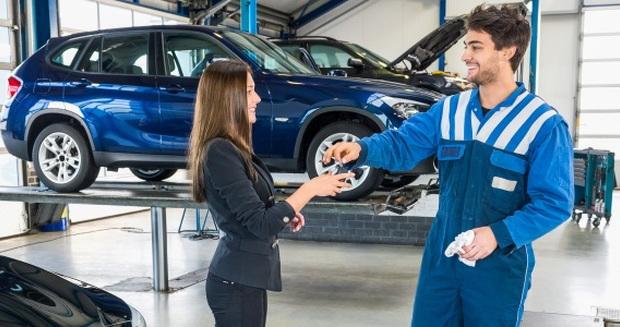 dealership service department, mechanic giving keys to customer