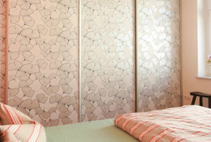 A small bedroom with wallpaper on closet doors.