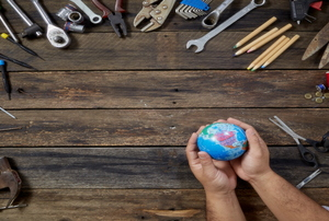 A pair of hands holding a small globe with a bunch of tools surrounding it.