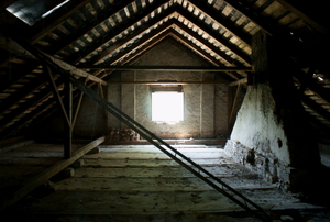 An empty attic with light coming through a window.