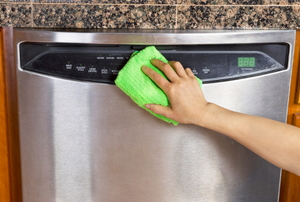 Wiping down the front panel of a stainless steel dishwasher.