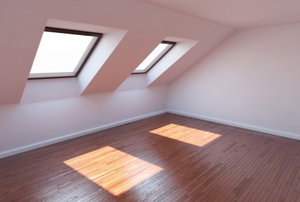 Windows casting patches of light on a wooden attic floor.
