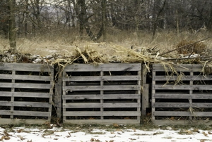 A trio of wood compost bins outside in the winter snow.