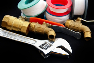 A grouping of plumbing tools including thread seal tape, a wrench, and pipe fittings.