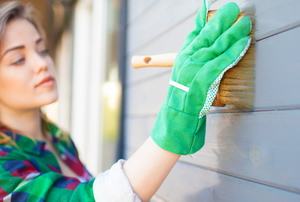 woman painting house exterior siding