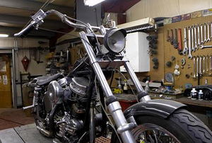 A motorcycle sitting inside a workshop.