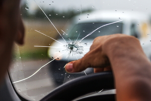 person driving car with cracked windshield
