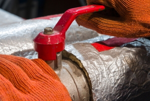 gloved hands adjusting insulated water heater