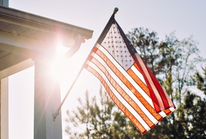 American flag hanging on house porch
