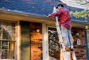 A man standing on a ladder in front of a house cleaning out the gutters.