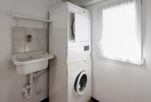 stackable washer dryer unit in the corner of a room