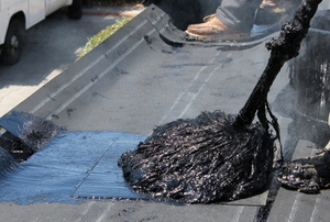 applying hot roofing tar with a mop