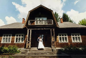 A bride and groom posing in front of a rustic farmhouse.