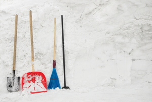 A set of snow removal tools, including a shovel and broom, against a snowy background.