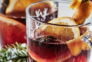 red wassail drinks with sliced citrus fruit and cinnamon