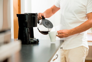 A man uses a coffeemaker.