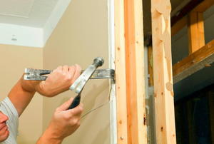 Using a pry bar and hammer to remove sheetrock