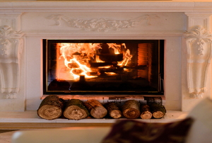 A white fireplace with a fire in it.