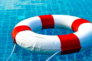 A lifeguard safety ring floating in a pool.