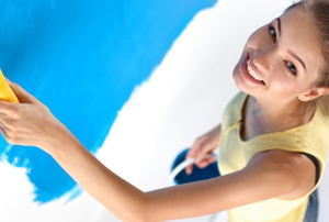 Woman applying blue paint to a wall.