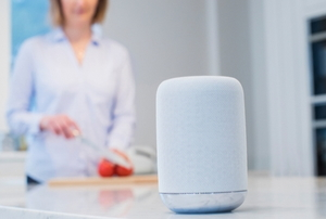 a woman cuts fruit in a kitchen with a smart home hub