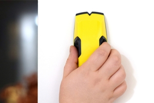 hand using stud finder on wall