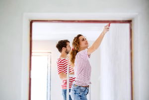 A young couple painting the inside of a house.