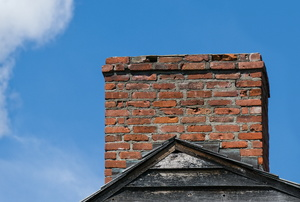 A brick chimney in front of a blue sky.