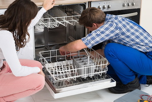 man and woman looking inside an open dishwasher