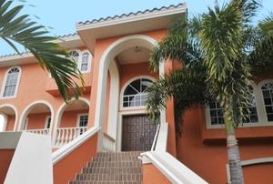 a stucco home near palm trees