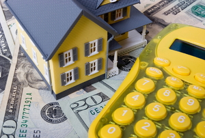 A yellow calculator with cash and a small plastic house.