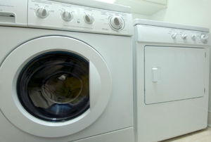 A white dryer sitting in a laundry room.