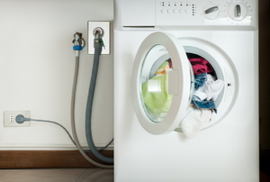 Hoses and and cords connect a washer to a wall.