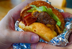 two hands holding a burger in tinfoil